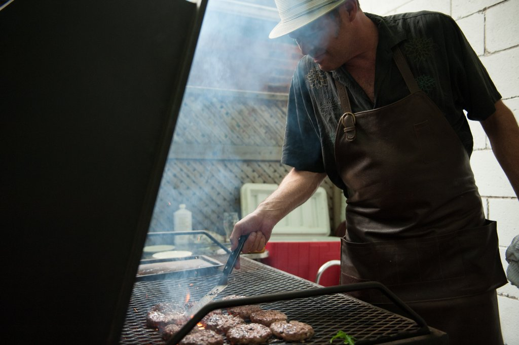 Mat grilling up some juicy lamb burgers over charcoal